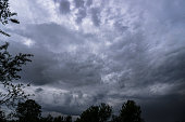 istock Scary thunderclouds and black trees. Night storm and dark cloud. Dark heaven background 1285814031