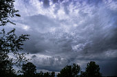 istock Scary thunderclouds and black trees. Night storm and dark cloud. Dark heaven background 1285814086