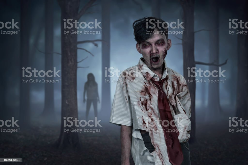 Scary two asian zombies with wounded face on the forest at night
