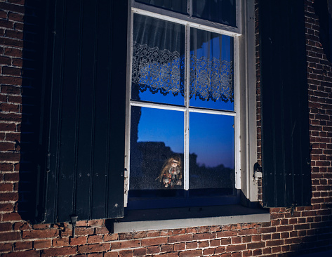 Scary vintage china doll behind window of old house at dusk.