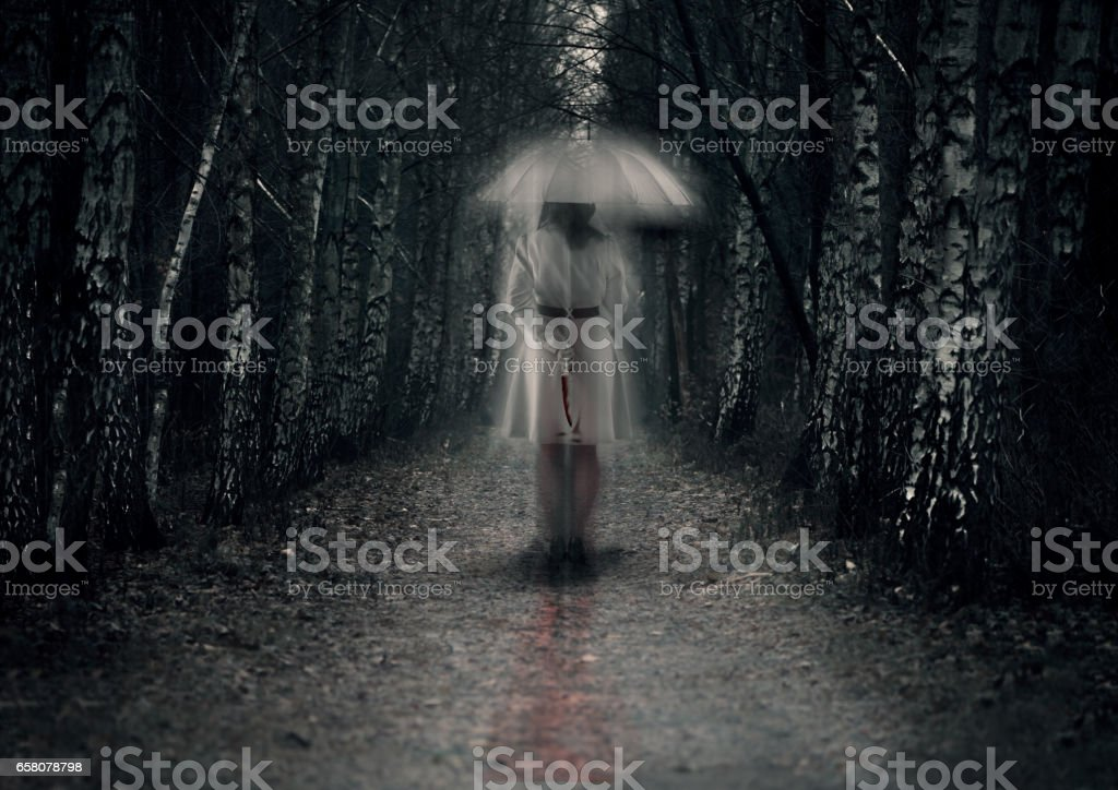 Scary woman ghost with knife stays in dark forest path royalty-free stock photo