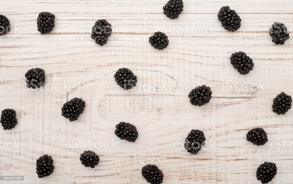 Scattered blackberries on a wooden light background stock photo