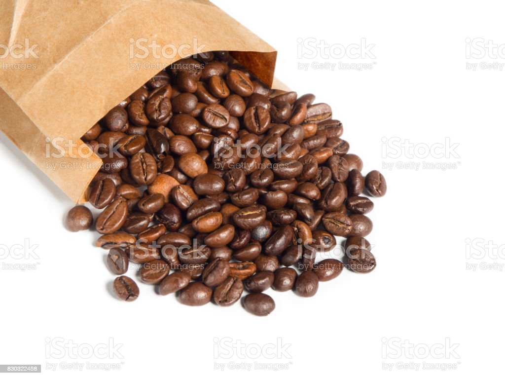 Scattered coffee grains from brown paper bag over isolated white background stock photo