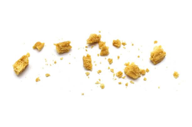 briciole sparse di biscotti al burro su sfondo bianco. - briciola foto e immagini stock