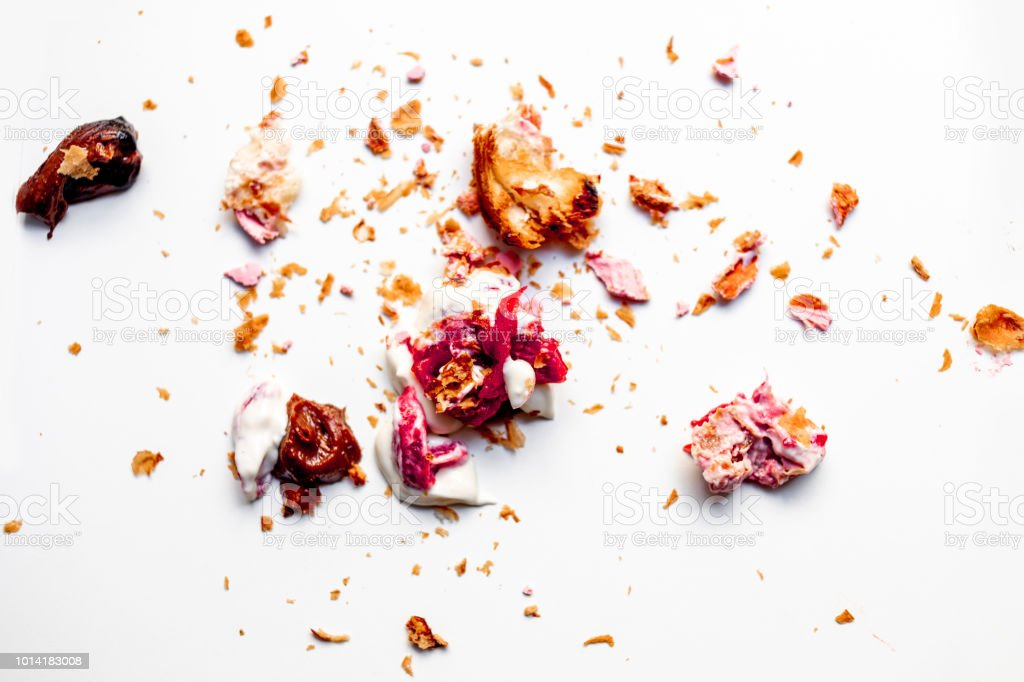 Scattered crumbs of cookies and croissant   isolated on white background. Broken Pastry Macro. Flat lay stock photo