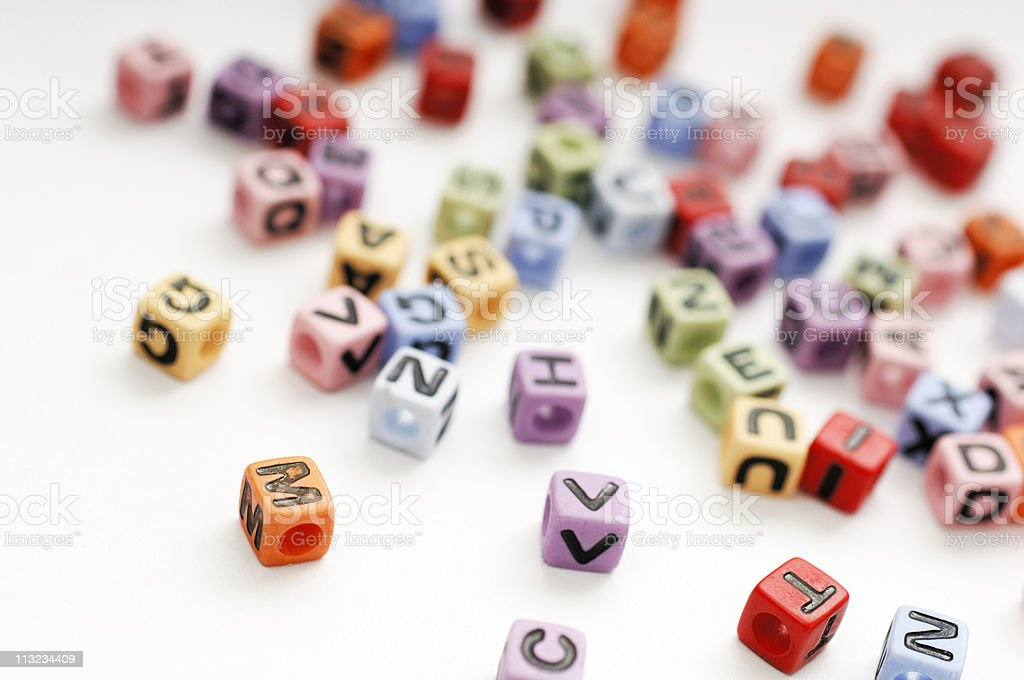 Scattered cubed beads of alphabet letters against white royalty-free stock photo