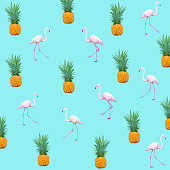 istock Scattered Flamingo birds and pineapples  background 1286269588