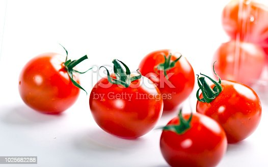 Scattered fresh ripe cherry tomatoes on a white background
