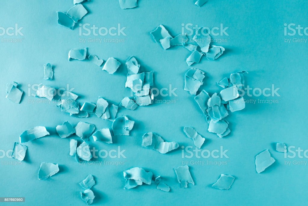 Scattered paper shreds on blue stock photo