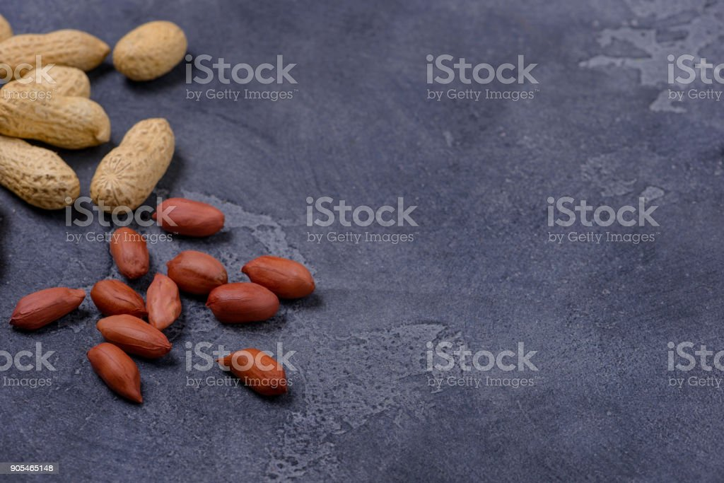 Scattered peanuts on dark stone background stock photo