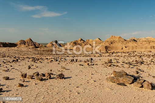 Scattered Rocks Across Foreground with Badlands Formation Behind