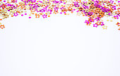 istock Scattered round confetti and in the form of flowers pink, gold and orange color on a white background. Copy space. Spring and summertime, birthday and wedding concept 1214692047