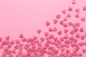 istock Scattered sugar pink hearts on a pink background 932732434