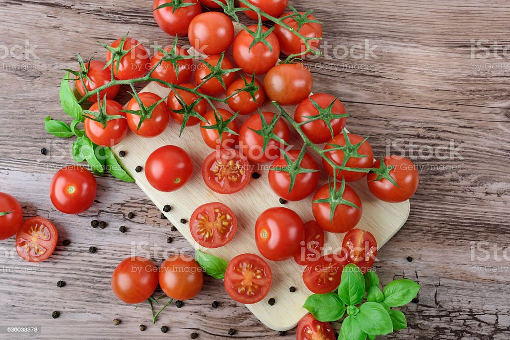 Scattered tomatoes on the wooden table. – zdjęcie