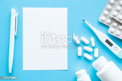 istock Scattered white pills from bottle, packages of medicines, thermometer and pen with blank paper sheet for list or prescription. Cold and flu time. Pastel blue background. Empty place for text. 1137270662