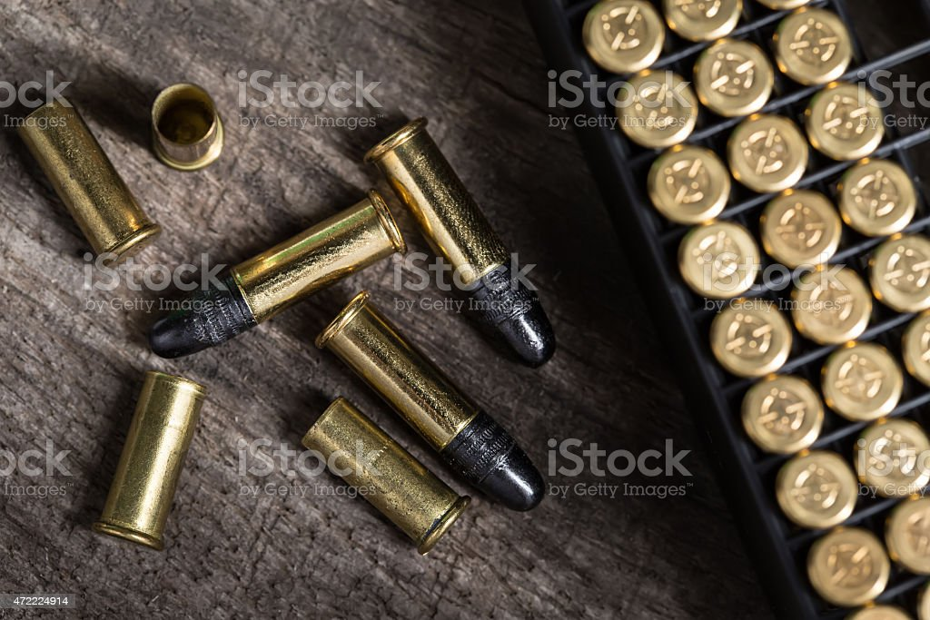 Scattering of small caliber cartridges on a wooden background stock photo