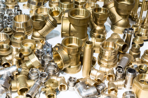 Scattering of various brass sanitary products. Scattering of various brass sanitary products. Abstract industrial background. coupling device stock pictures, royalty-free photos & images