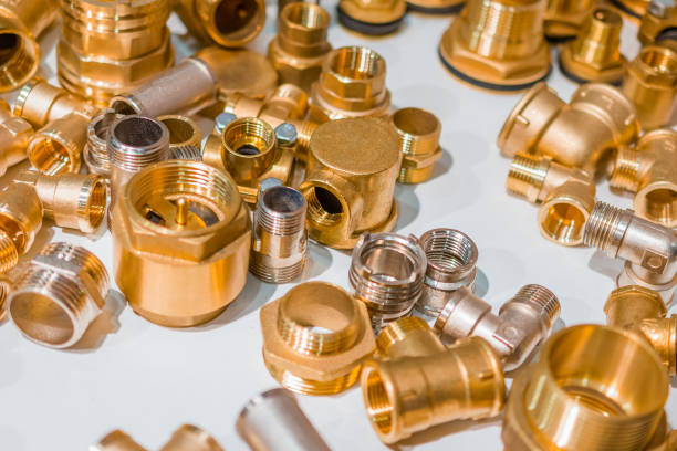 Scattering of various brass sanitary products Scattering of various brass sanitary products. Tees, branch pipes, connectors, nipples. Abstract industrial background. coupling device stock pictures, royalty-free photos & images