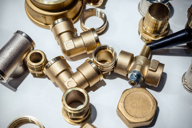 Scattering of various brass sanitary products Scattering of various brass sanitary products. Abstract industrial background. coupling device stock pictures, royalty-free photos & images