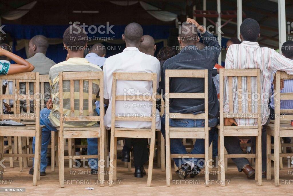 Escena de detrás de los hombres sentados en sillas en el servicio de la iglesia Burundi Bujumbura - Foto de stock de Adulto libre de derechos
