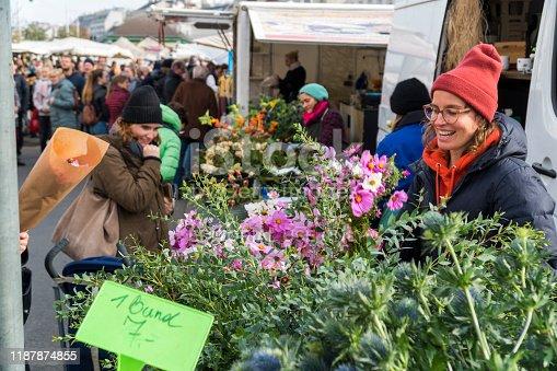 Vienna, Austria, traditional city market Naschmarkt, 11/02/2019. Smiling cute flower girl working on her flower stand.