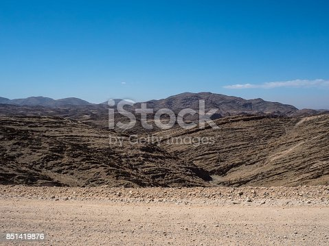 istock Scene of great rock mountain texture layers panorama landscape view background and clear blue sky on unpaved dirt road 851419876