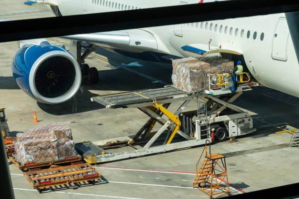 scène van ladings bagage en lading aan vliegtuig met behandelings verrichtingen in luchthaven, reis en vervoer concept - airport pickup stockfoto's en -beelden