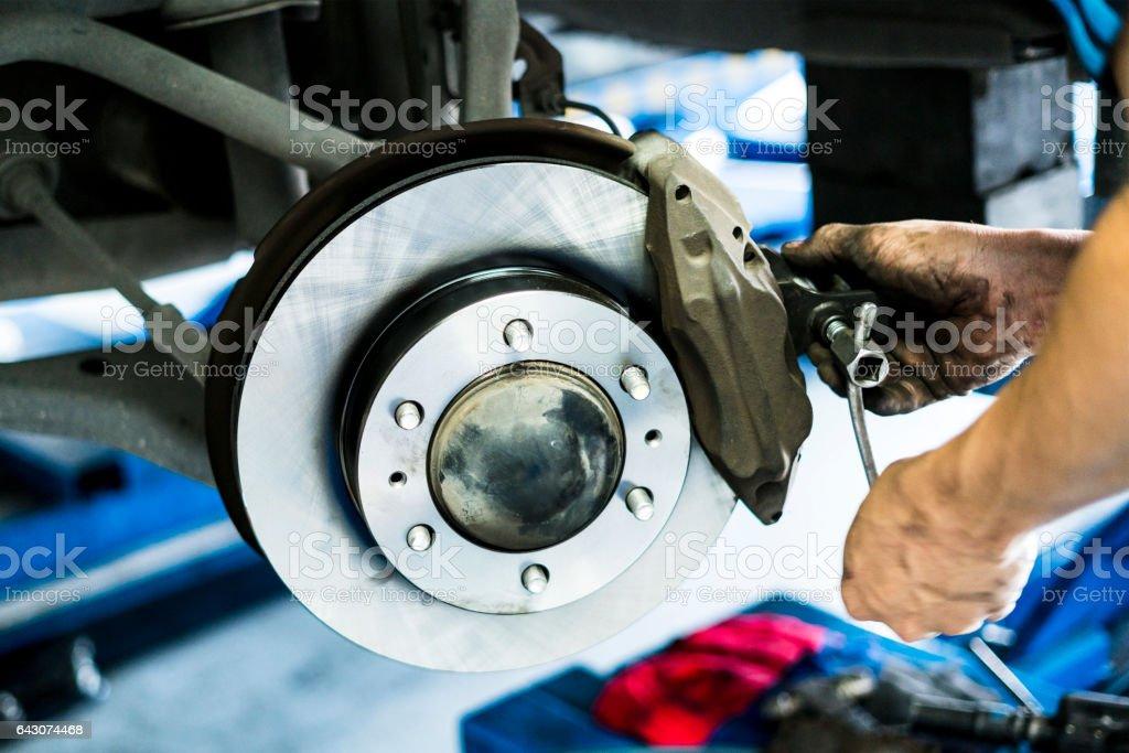 Scene of mechanic assembling Car DiscBrake stock photo