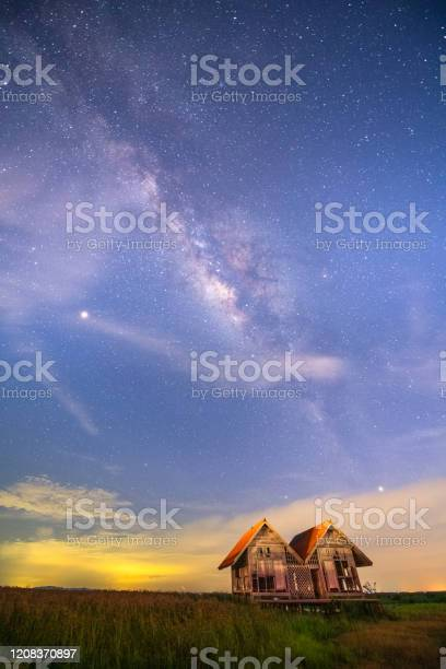 Photo of Scene of milkyway galaxy night sky and meadow rice field background Phatthalung province, Thailand