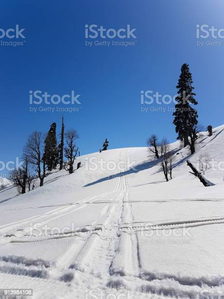 Photo of scene of snow mountain with intersect tracks of snowmobile