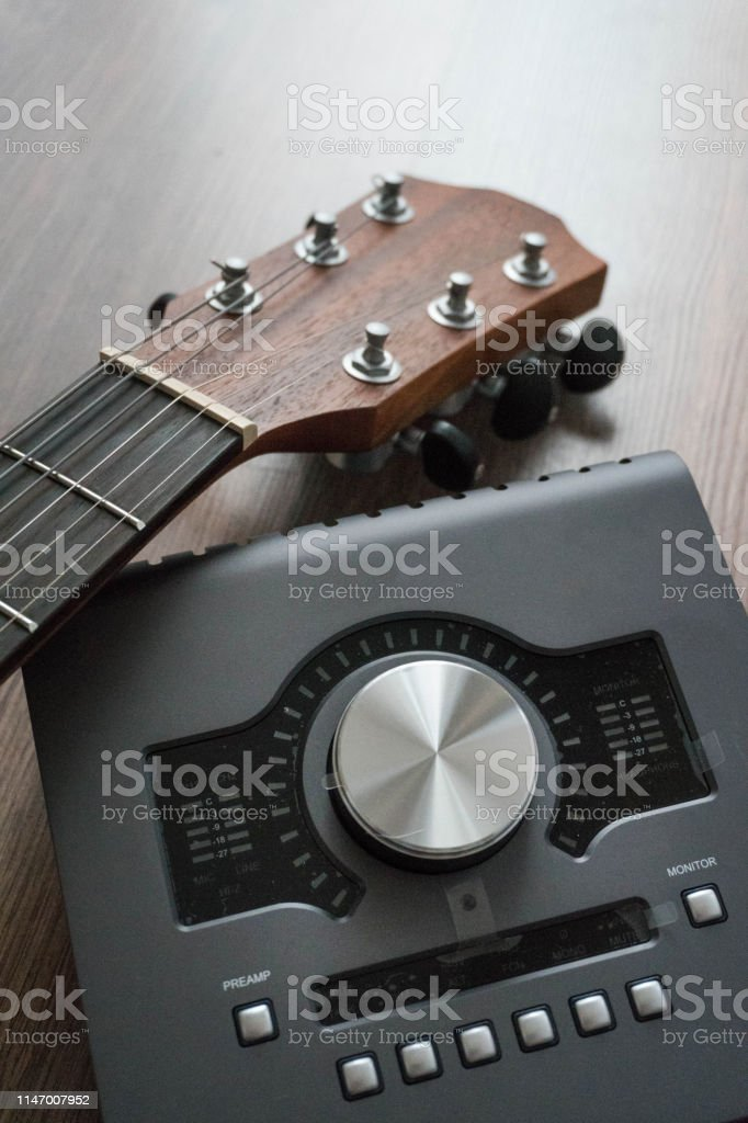 Scene of sound designers tools on dark wood table: sound card,...