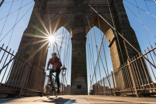scene of stop motion bicycle with brooklyn bridge when sunrise, usa downtown skyline, architecture and building with tourist concept - stop motion stock photos and pictures