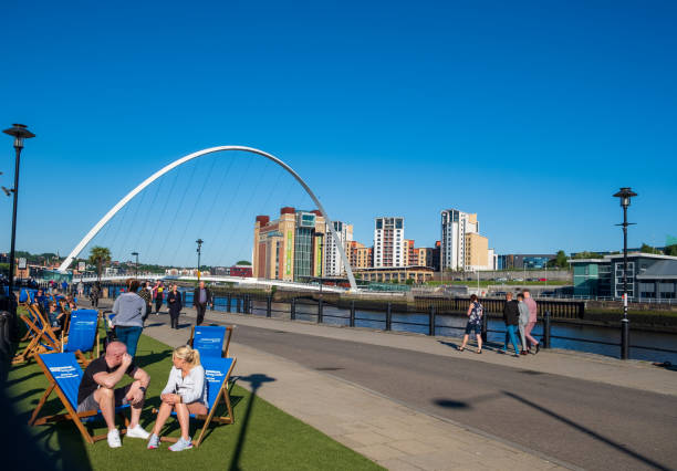 Scene set against the Gateshead Millennium Bridge and the Baltic Centre for Contemporary Art of people enjoying themselves at the Newcastle Quayside on a beautiful summer afternoon. stock photo