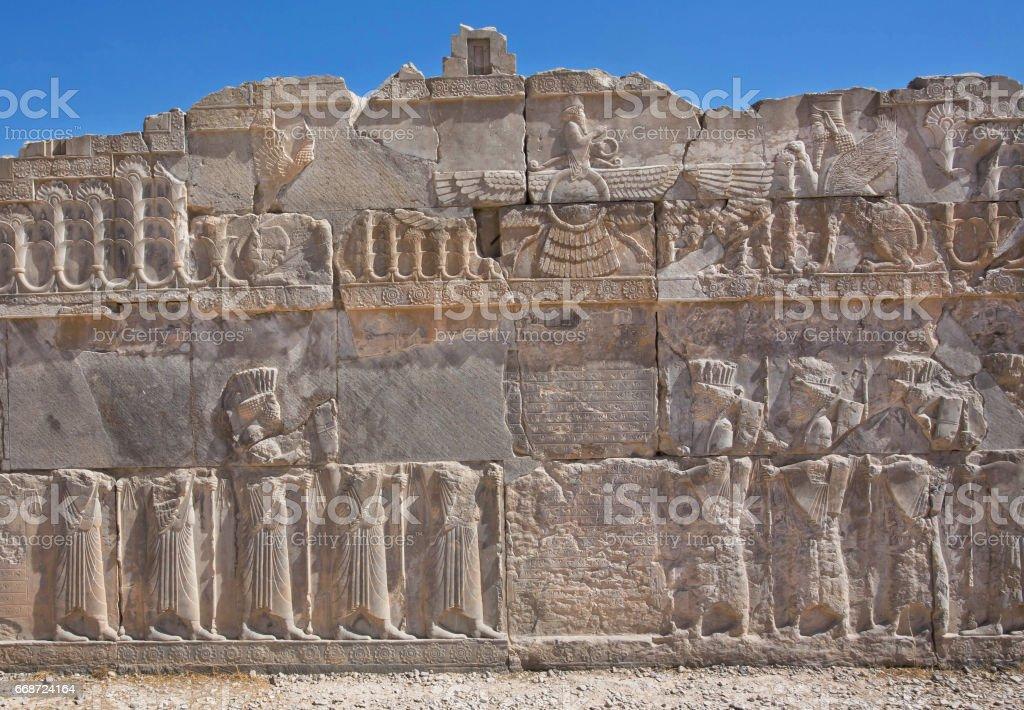 Scene with Faravahar - relief of winged sun symbol of Zoroastrianism in ruined Persepolis stock photo