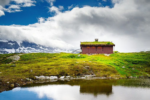 Scene with lonely rural home at hill top, built in Scandinavian construction design tradition - nature friendly design, house with grass at the roof. Located at lake bank. Norway, Scandinavia, Europe.