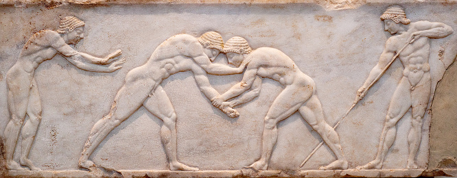 Ancient bas-relief on ancient Greek funerary stele from Kerameikos in Athens, Greece. Scene from Palaestra - wrestlers in action. On the left an athlete is ready to jump, on the right another one prepairing the pit.