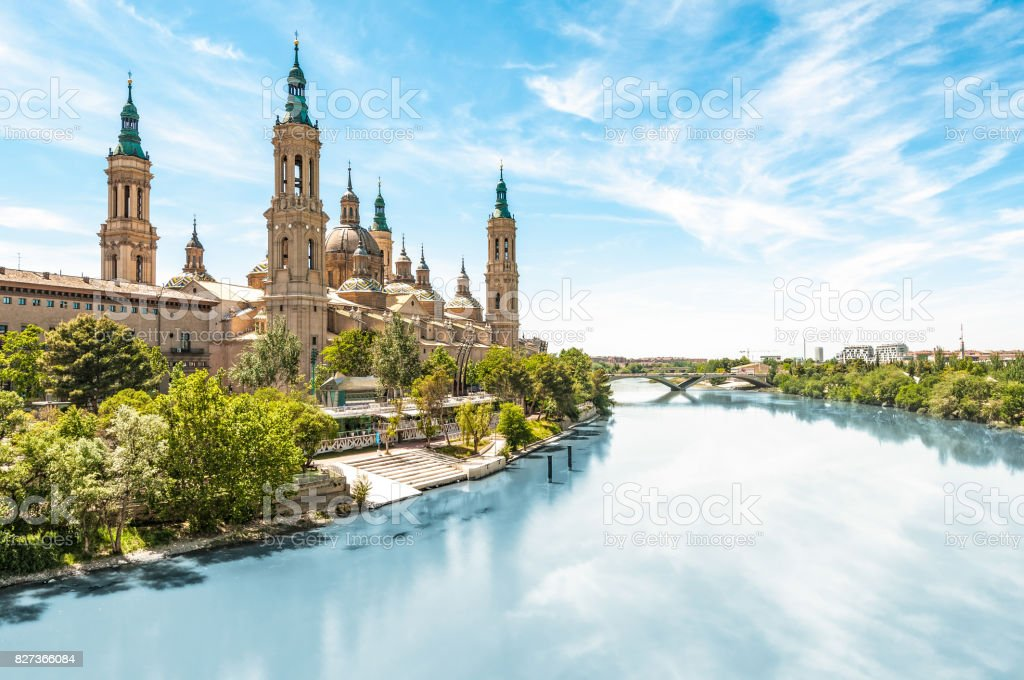 Scenery landscape with Basilica of Our Lady of Pillar. Blue sky reflects in clear water. Green trees along river. Famous church with beautiful architecture. Famous tourist place in Spain, Europe. stock photo