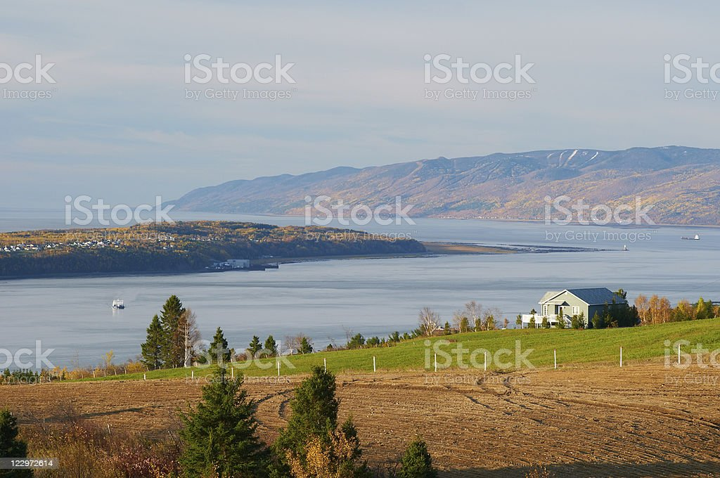 Scenery of the lake and green grass with farm in Quebec stock photo