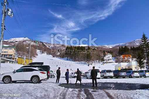 Yamagata, Japan - 7 March 2018: Scenery of Zao central ropeway hot spring station parking lot in winter. The car is for skiing and snowboarders. In this ropeway, ski / snowboarders are mostly able to climb up to the central slope of the main ski slope of Zao Onsen ski resort. In the center of the photo, bus guides and drivers are looking at the slopes.