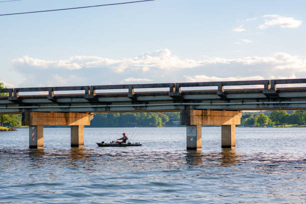Scenery on a lake in upstate S.C. Inman, S.C. / USA - May 5. 2019: A man goes fishing under a bridge at sunset, on Lake Bowen, a man-made reservoir in Spartanburg County in upstate South Carolina. spartanburg stock pictures, royalty-free photos & images