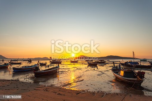scenic reflection of beautiful sunshine in the sea fishing boats are floating in the Rawai sea