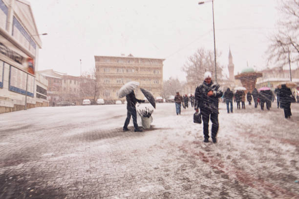 Scenes from everyday street life in Turkey. Umbrella seller and pedestrians on a snowy day stock photo