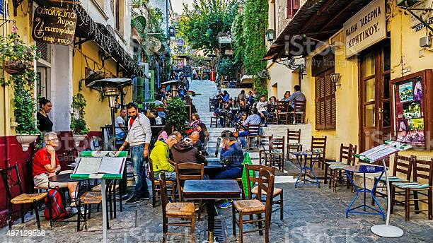 """Athens, Greece - November 6, 2015: Scenes from Plaka, also called """"Neighbourhood of the Gods"""", the old district of Athens at the foot of the Acropolis with labyrinthine streets and neoclassical architecture."""