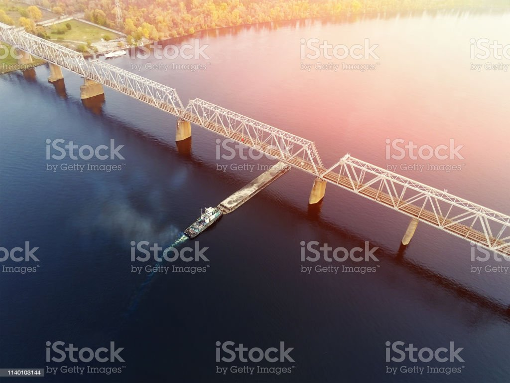 Scenic aerial cityscape of Kiev and river Dnipro at sunset. Tugboat...