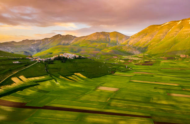 Scenic aerial view of a countryside landscape with lots of patchwork fields and beautiful green rolling hills, Castelluccio, Umbria, Italy stock photo