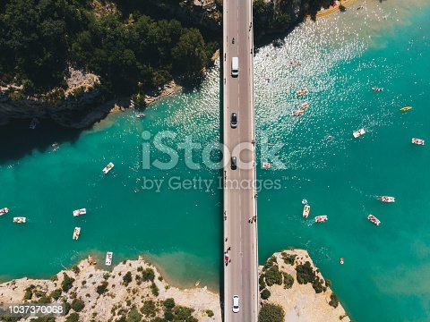 Scenic aerial view of boats on  Verdon lake and cars on the bridge in France