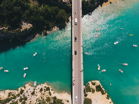 Scenic aerial view of boats on  Verdon lake and cars on the bridge