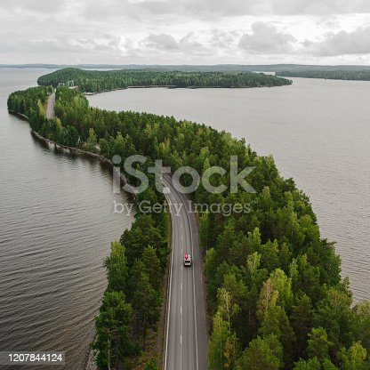 istock Scenic aerial view of camper van with canoe on roof on road through the lake in Finland Lakeland 1207844124