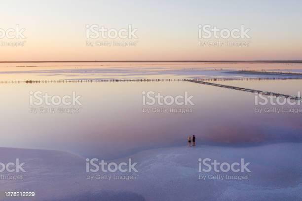Photo of Scenic aerial view of heterosexual walking on  pink salt lake