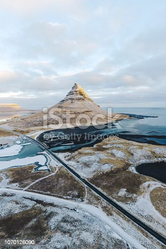 Scenic aerial view of Kirkjufell mountain in Iceland and seaside in winter